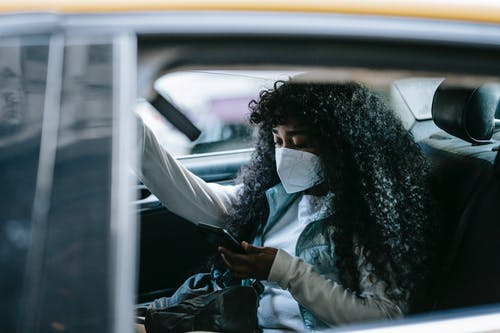 Focused black woman in medical mask browsing smartphone in car