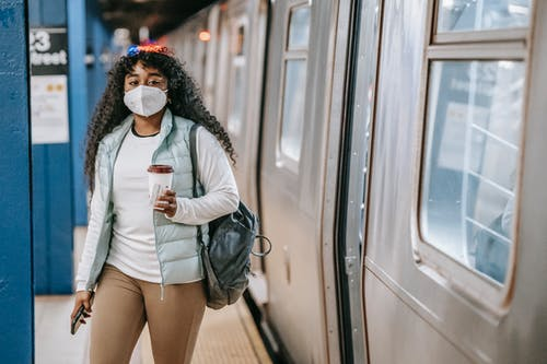 Calm black woman with coffee wearing medical mask standing in metro