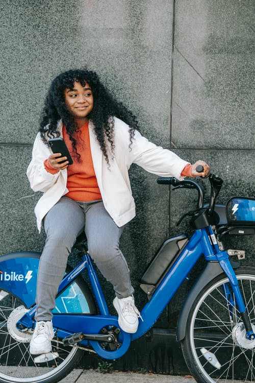 Full body of African American female browsing cellphone and looking away while sitting on bicycle near wall on city street