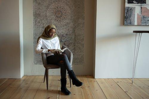 Focused black Muslim woman reading book on chair