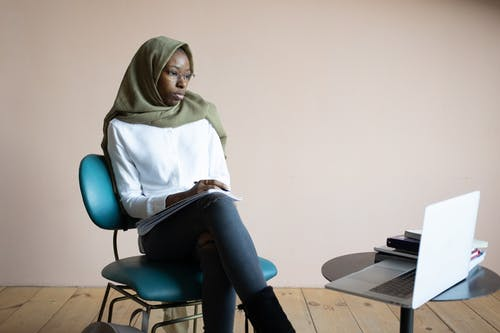 Focused African American Muslim female in hijab and headscarf taking notes and watching educational video on netbook while sitting on chair in light room