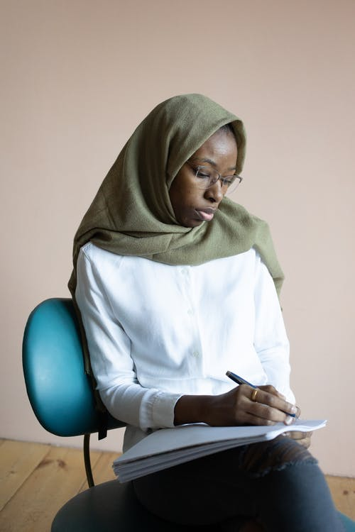 Serious young African American Muslim female wearing casual outfit hijab and eyeglasses taking notes in copybook while sitting on chair in light room