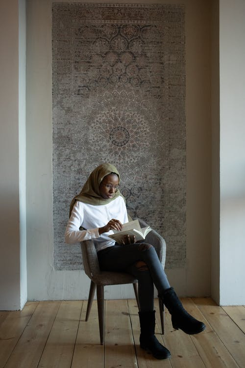 Full body focused African American Muslim female in traditional hijab and casual wear reading interesting story and sitting with legs crossed on armchair in light room