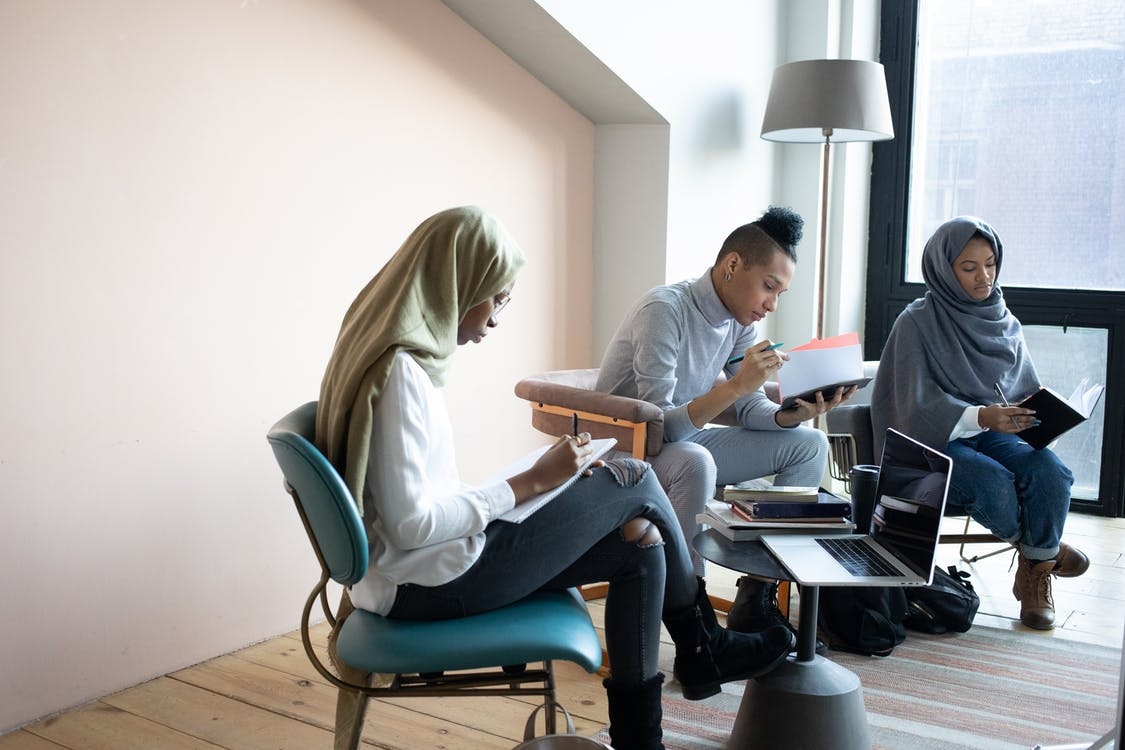 Focused multiethnic students writing in copybooks in coworking space