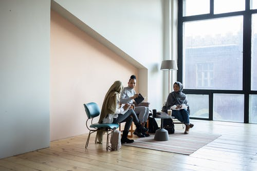 Full body young multiracial coworkers or students with stationery and books discussing project while sitting on chairs in light modern coworking space