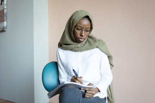 Serious black Muslim woman writing in notebook