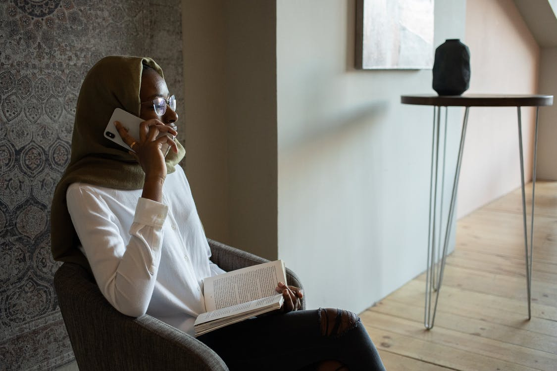 Unemotional African American Muslim female in white shirt eyeglasses and hijab sitting on armchair with book and having conversation via mobile phone in modern apartment