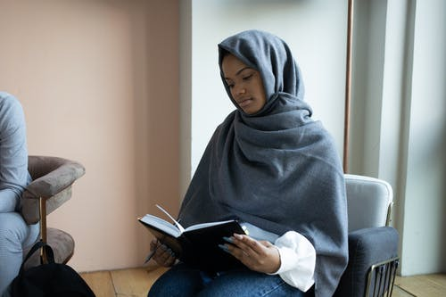 Concentrated young Muslim female in traditional headscarf reading novel and sitting on armchair in light room