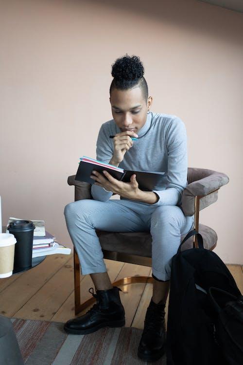 Ethnic man reading notes in copybook in studio