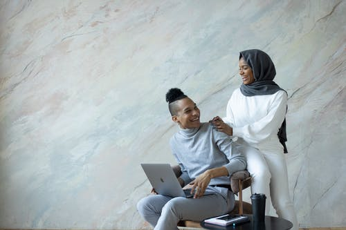 Joyful young ethnic friends in casual clothes using contemporary netbook while sitting on comfy chair and looking at each other with happy smiles