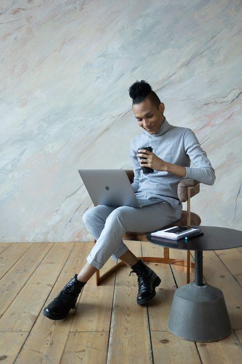 Hombre Con Camisa De Manga Larga Blanca Y Pantalón Gris Sentado En Una Silla Con Macbook