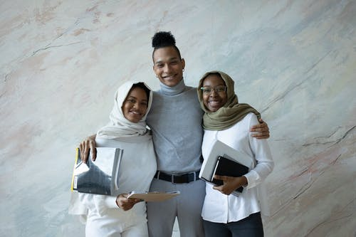 Cheerful black students with documents standing close
