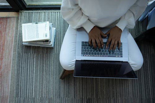 Top view of anonymous African American female student sitting with crossed legs and typing on netbook sitting near stack of books