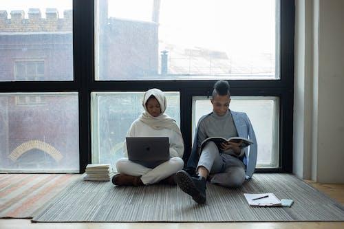 Serious black classmates doing homework together near panoramic window