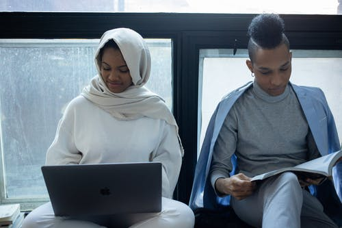 Concentrated African American woman in hijab working on laptop near classmate reading textbook during exam preparation