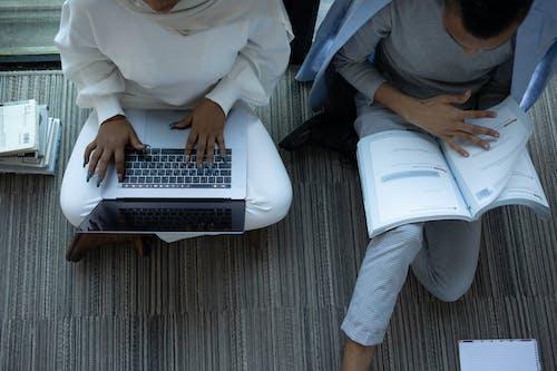 Persona Con Camisa De Vestir Blanca Y Pantalón Gris Sentado En Una Silla Rodante De Oficina Negra