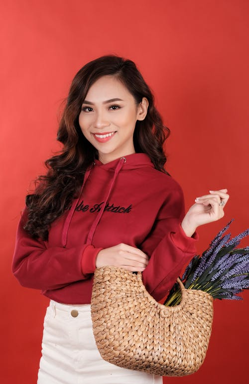 Positive female in stylish casual outfit smiling happily standing with bag of lavender flowers against red background and looking at camera