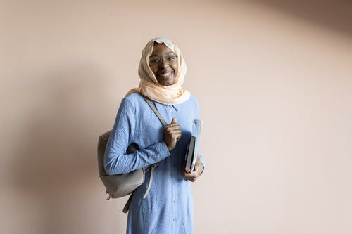 Muslim female in hijab with textbook and backpack