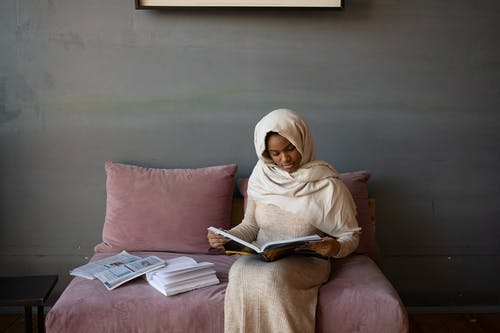 Serious black woman reading journal sitting on sofa