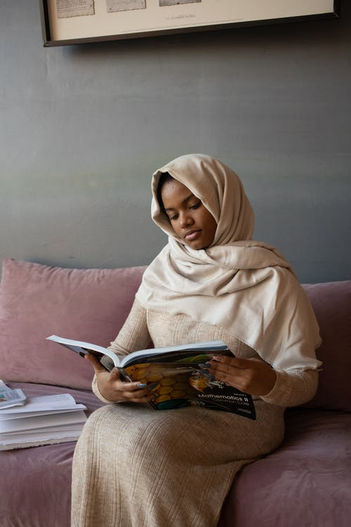 Concentrated African American female in traditional hijab reading magazine sitting on couch at home