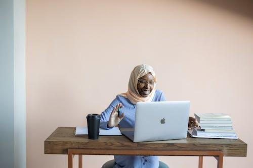 使用macbook的藍色長袖襯衫的女人