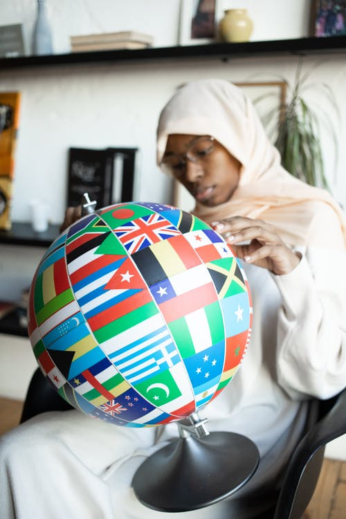 Concentrated African American female in traditional Muslim clothes and eyeglasses finding flag of country on globe