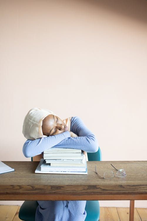Exhausted African American female student in hijab having nap on stack of textbooks after studies