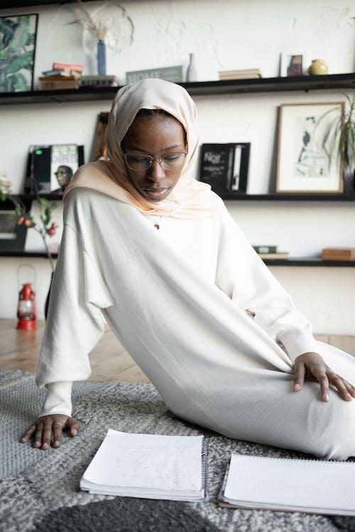 Black woman reading notebook on floor