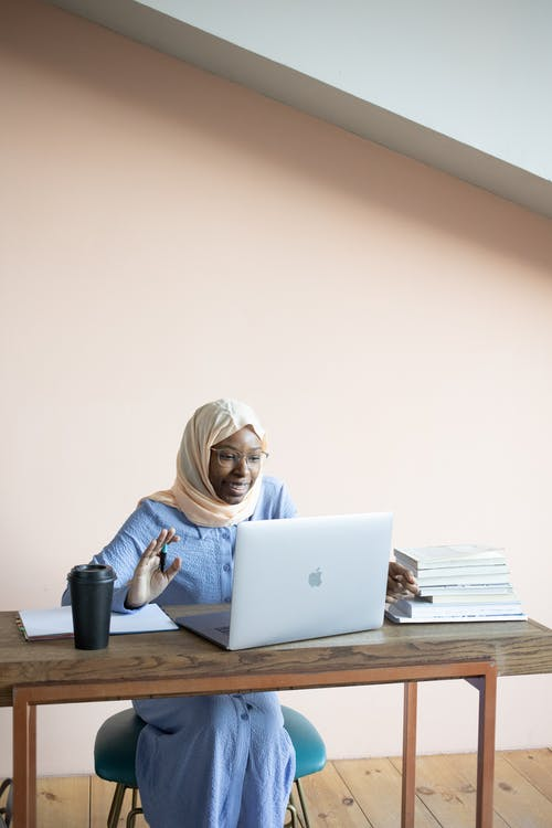 使用銀macbook的藍色長袖襯衫的女人