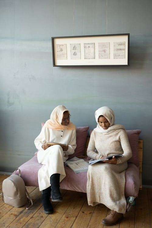 Black women reading book together on sofa
