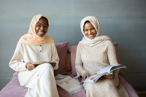 Smiling African American woman with clipboard sitting near friend turning page of book sitting on sofa
