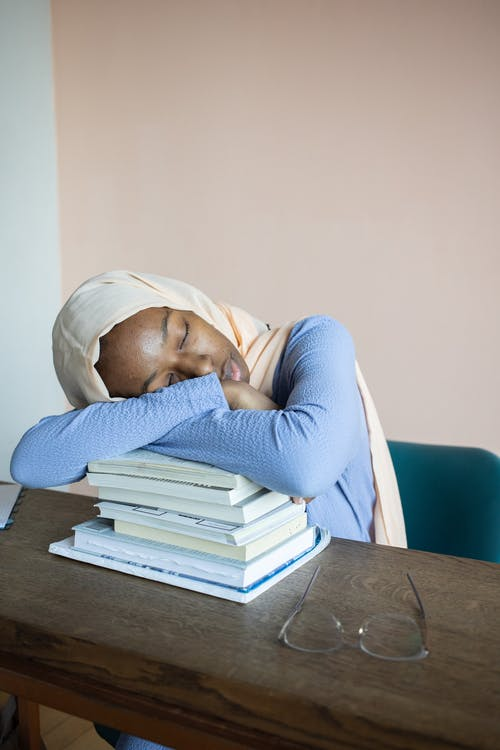 Tired black woman resting on books after studies