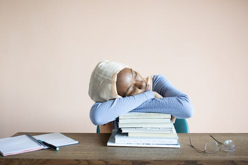 Sleeping African American female student in headscarf sitting at table with opened notebook and lying on stack of textbooks