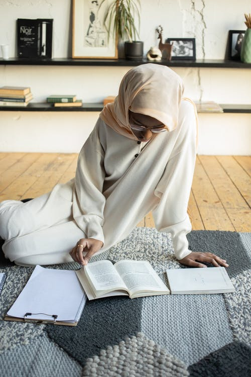 High angle of African American female in hijab and eyeglasses sitting on floor carpet with clipboard and notebook and reading book