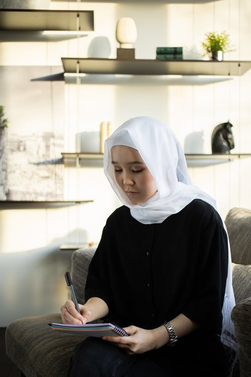 Serious ethnic female in traditional hijab writing plans in planner sitting on sofa in living room