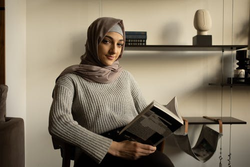 Young positive Muslim female in headscarf and sweater reading book and looking at camera while sitting in light modern apartment