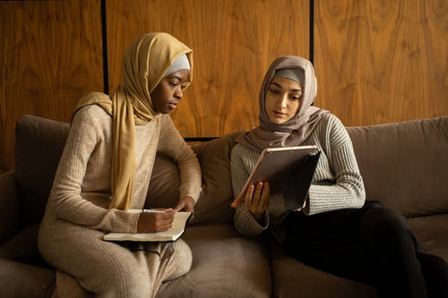 Multiethnic Muslim women using tablet and taking note