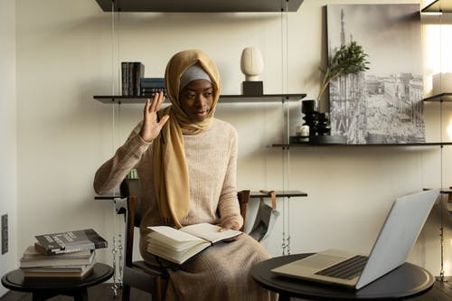 Positive Muslim African American female clerk in hijab raising arm in greeting gesture while having video call through netbook while working from home office