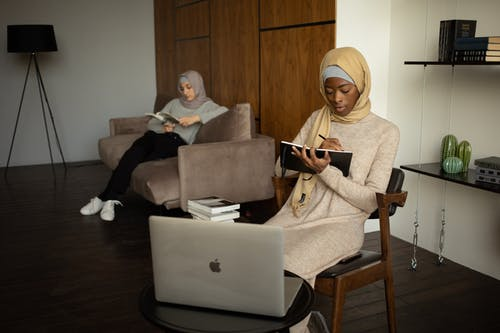 Focused young black Muslim female taking notes and watching tutorial via laptop near female friend reading book on sofa