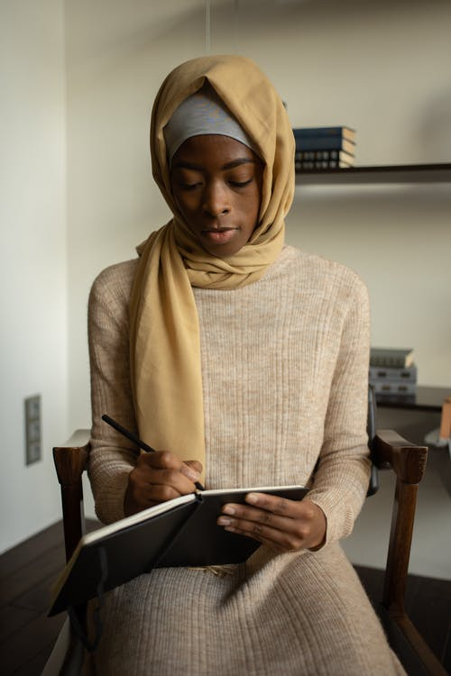 Serious African American Muslim female in headscarf and warm dress taking notes in planner while sitting on chair in apartment