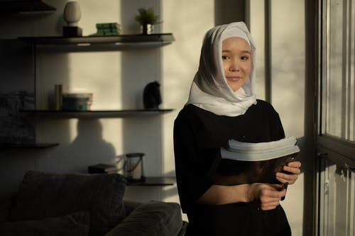 Smiling Muslim woman standing with textbooks in living room