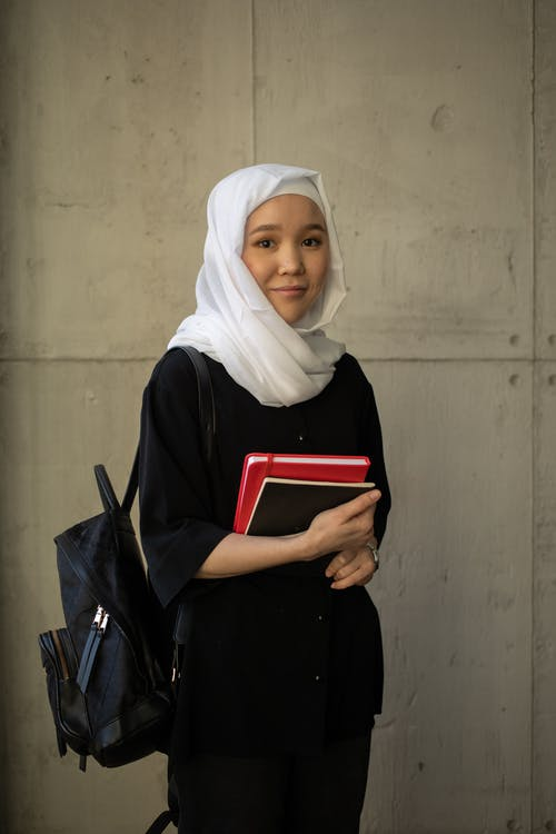Positive young Muslim female student in black outfit and white hijab holding books and backpack while looking at camera and standing near building wall
