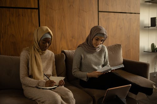 Concentrated diverse women in hijabs writing in copybooks while sitting on couch near tablet