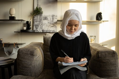Focused Asian woman in hijab writing in copybook