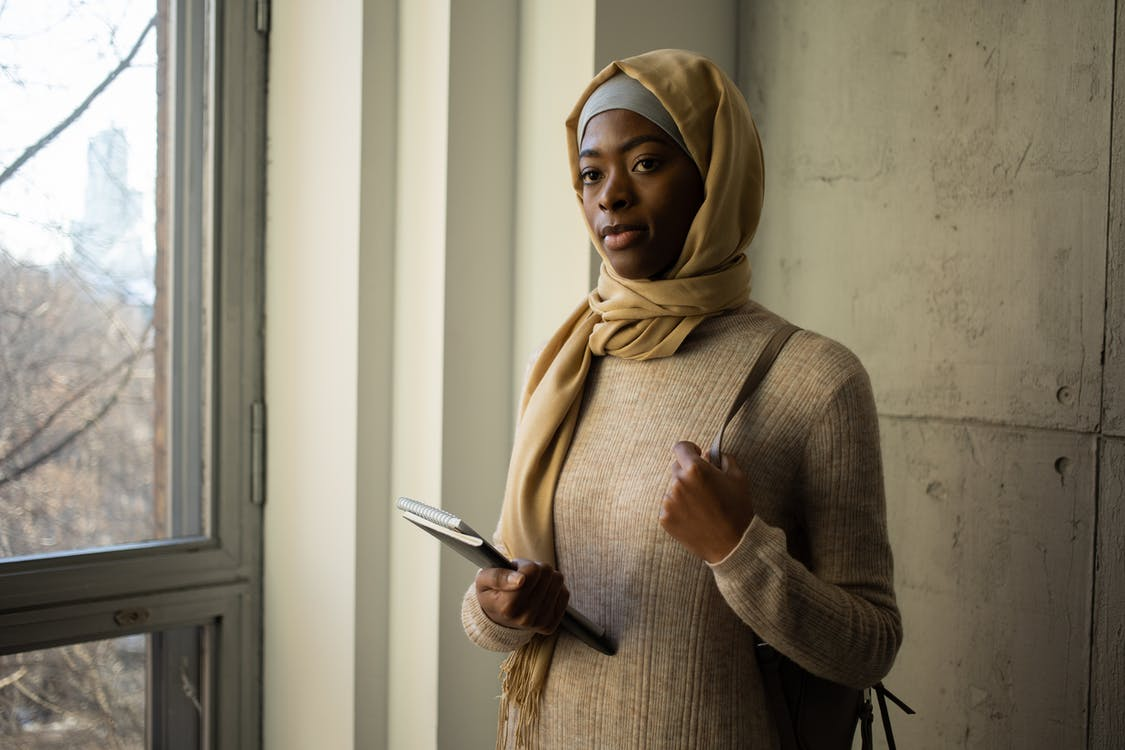 Calm Muslim female student in traditional headscarf looking away while standing with workbooks near wall in corridor of university during studies