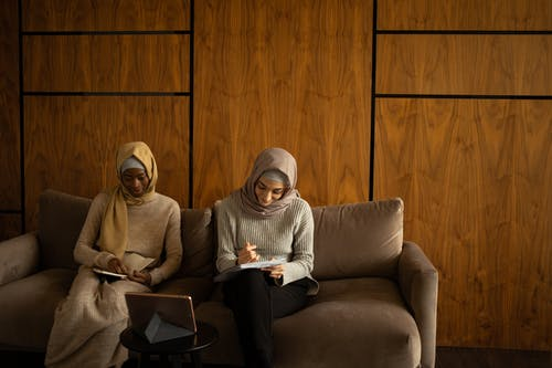 Cheerful diverse women in hijabs taking notes in workbooks on couch
