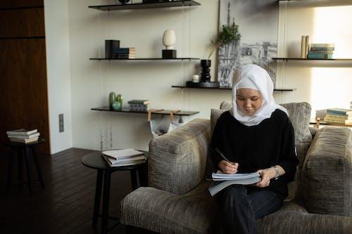 Muslim woman taking notes in copybook