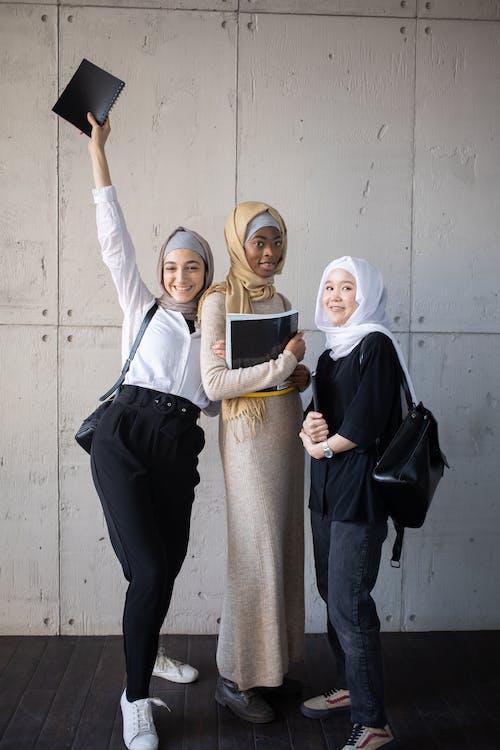 Happy multiethnic Muslim women in hijabs with workbooks in corridor of university