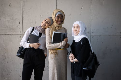 Delighted multiethnic female students in hijabs looking at camera while standing with backpacks and copybooks in hands near wall in corridor of university