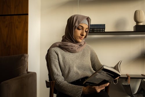Focused ethnic woman in hijab reading book in room